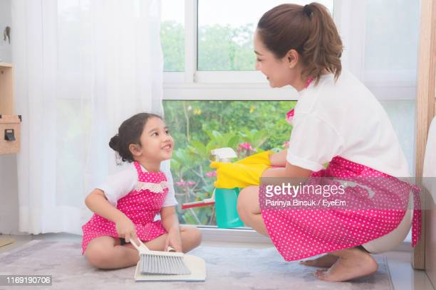 mother and daughter cleaning home - dustpan and brush stock pictures, royalty-free photos & images