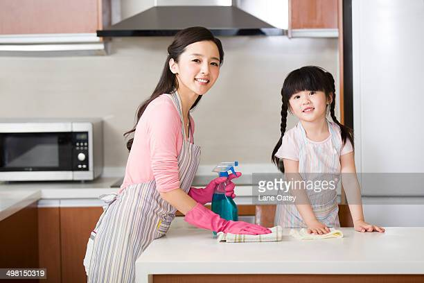 Mother and daughter cleaning kitchen counter