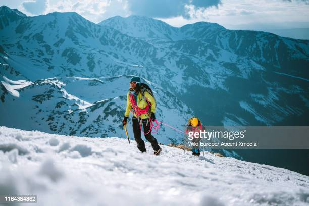 Mother and daughter climb up a mountain in winter
