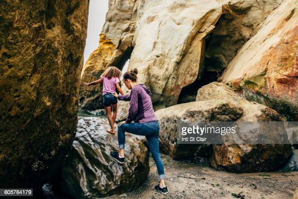 Mother and daughter climbing on beach rocks