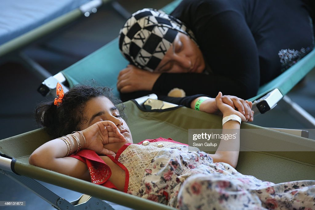 A mother and daughter clutch hands as they sleep on cots at a registration center for migrants at a facility of the German Federal Police (Bundespolizei) on August 31, 2015 in Rosenheim, Germany. German police monitor trains arriving from the Balkans and from Italy that go through Rosenheim and currently detain around 350 people a day for travelling without a passport. The police register the migrants, mostly from countries including Syria, Afghanistan and Eritrea, fingerprint them and check whether any are already in the European asylum-applicants or criminal databases. From there the migrants are free to travel within Germany to reception centers where they can apply for asylum. Up to 1,600 migrants are currently arriving in Bavaria in southern Germany a day and will seek asylum. Germany is expecting to receive 800,000 asylum-seeking migrants this year and is struggling to cope with the record number.