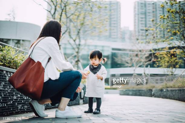 mother and daughter collecting dried leaves in urban park, they are enjoying family time on a lovely day - vida simples - fotografias e filmes do acervo