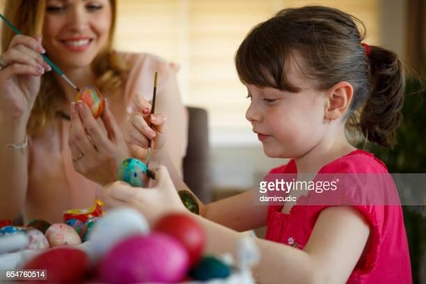 Mutter und Tochter zu Hause Ostereier färben