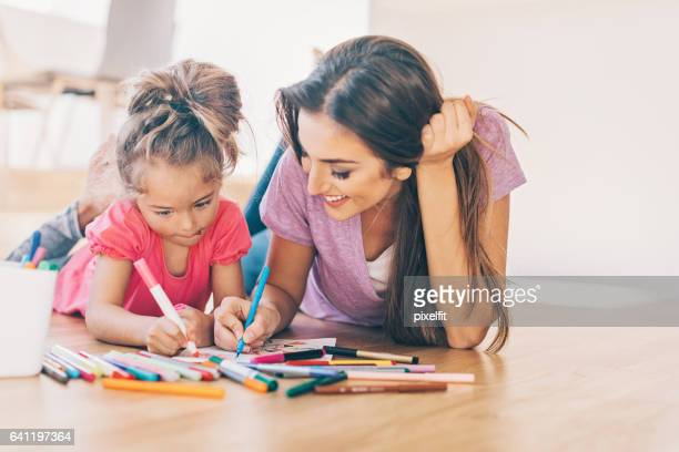 mother and daughter coloring on the floor - colouring stock photos and pictures