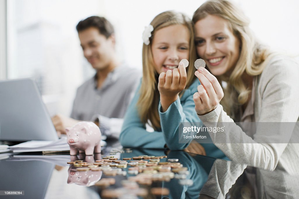Mother and daughter comparing coins : Stock Photo