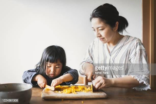 母と娘の家庭での料理 - preparing food ストックフォトと画像