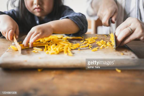 母と娘の家庭での料理 - 皮をむく ストックフォトと画像