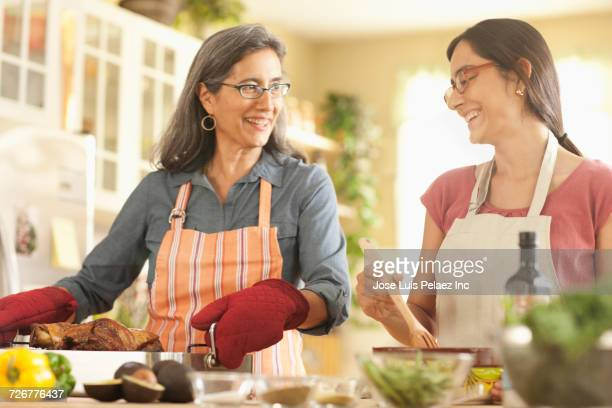 Mother and daughter cooking in domestic kitchen