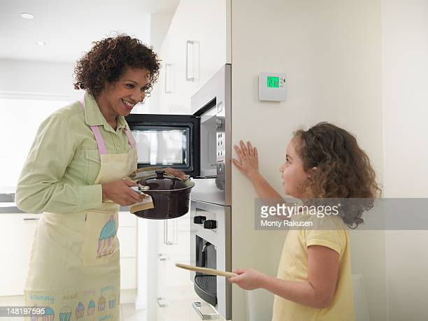 Mother and daughter cooking in energy efficient house