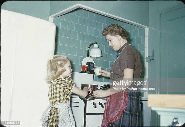 mother and daughter cooking in kitchen - archiefbeelden stockfoto's en -beelden