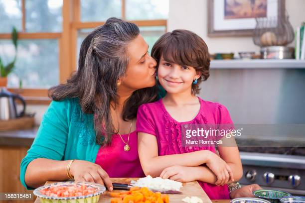 mother and daughter cooking in kitchen - indian girl kissing stock photos and pictures