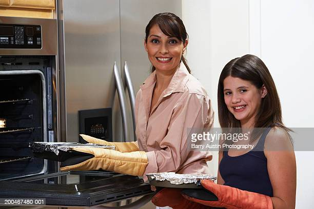 Mother and daughter (10-14) cooking, smiling, portrait