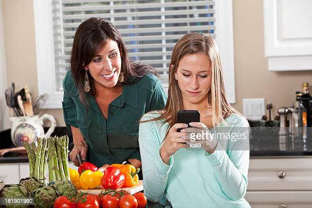 Mother and daughter cooking, texting