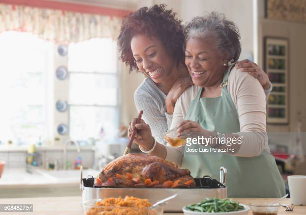 mother and daughter cooking together in kitchen - african american family home stock photos and pictures