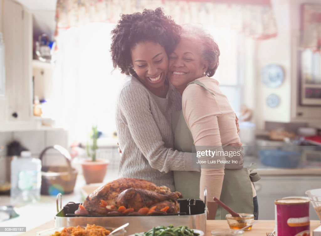 Mother and daughter cooking together in kitchen : Stock Photo