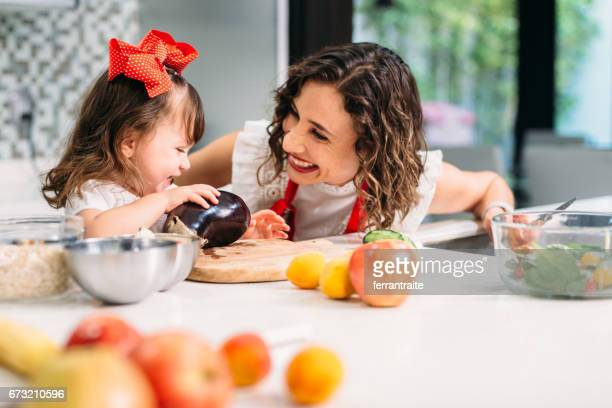 mother and daughter cooking together - nutritionist stock pictures, royalty-free photos & images