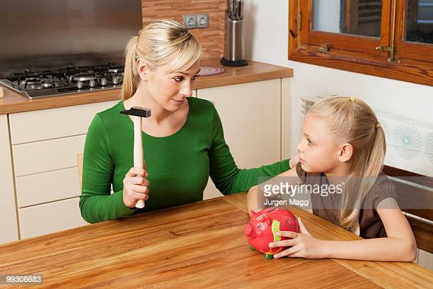 Mother and daughter crack a piggy bank
