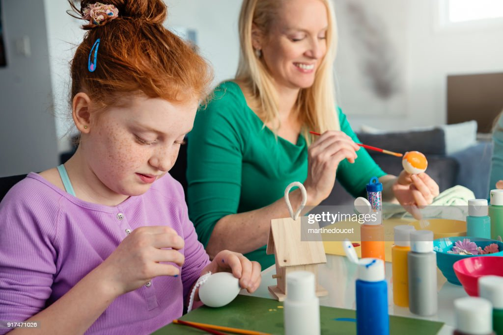 Mother and daughter crafting Easter decorations at home. : Stock Photo