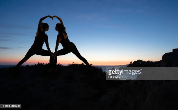mother and daughter creating heart doing yoga by ocean at sunset - i love you stock pictures, royalty-free photos & images