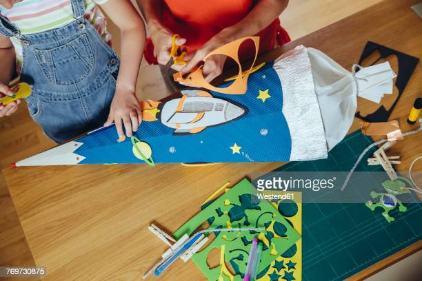 mother and daughter creating her space themed school cone at home - craft product stock photos and pictures