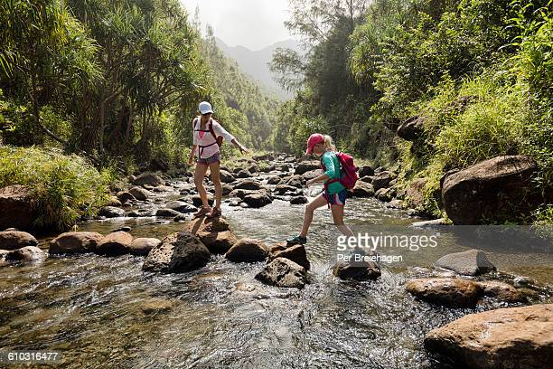 mother and daughter crossing a creek, kauai - state park stock pictures, royalty-free photos & images