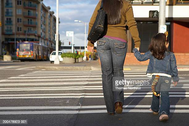 Mother and daughter (2-4) crossing street, holding hands, rear view