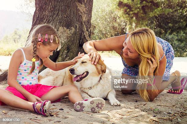 Mother and daughter cuddling a dog