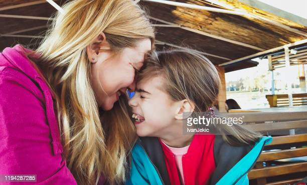mother and daughter cuddling outdoors - ivanjekic stock pictures, royalty-free photos & images
