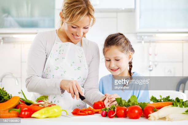 Mother and daughter cutting vegetables in the kitchen.
