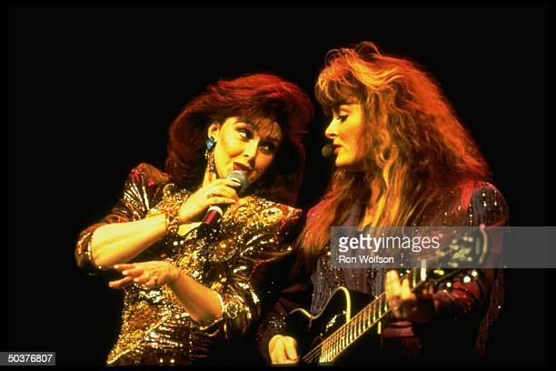 Mother and daughter C/W duo Naomi and Wynonna Judd singing in concert