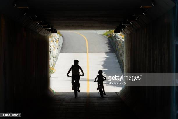 mother and daughter cycling to school - daughters of darkness stock pictures, royalty-free photos & images
