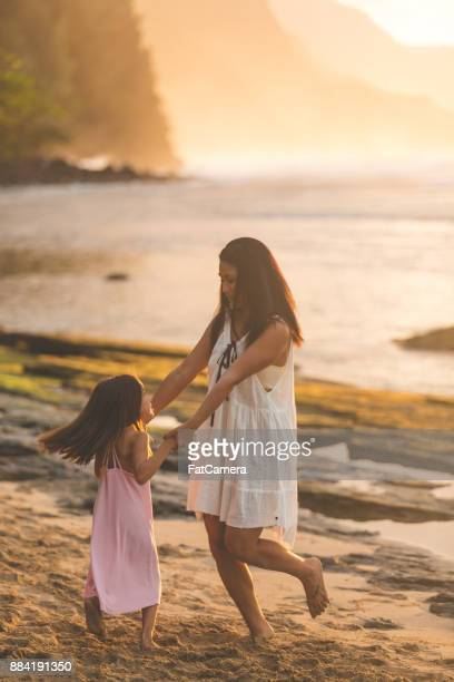Mother and daughter dance and play in the sand together