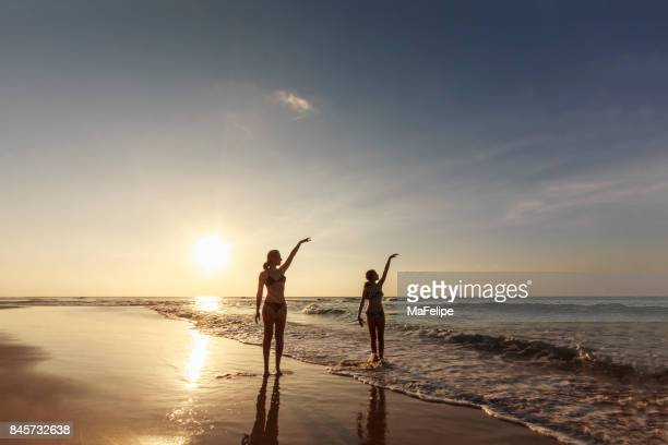 Mother and daughter dancing ballet at idyllic deserted beach