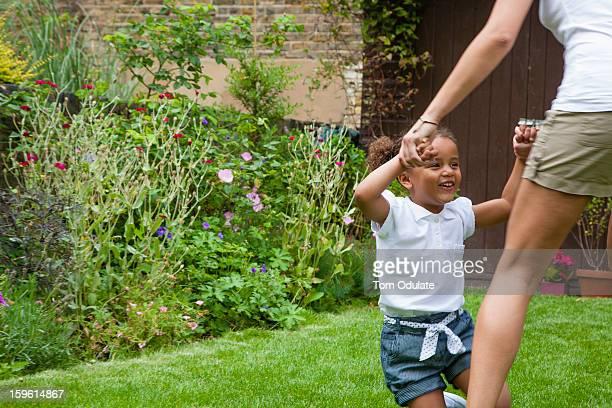 Mother and daughter dancing in garden