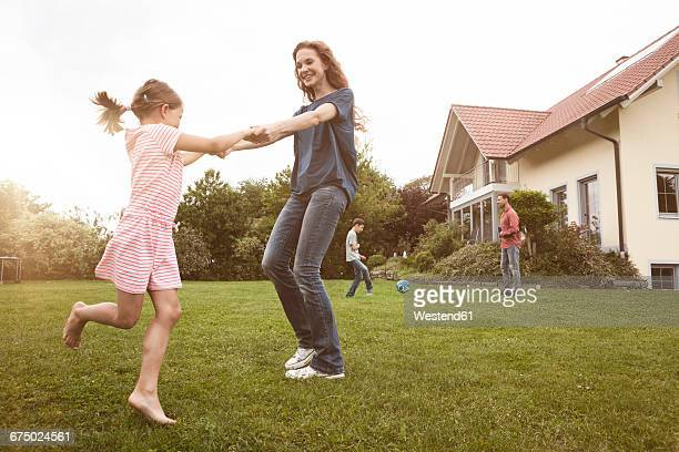 Mother and daughter dancing in garden with family in background