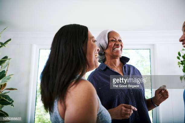 mother and daughter dancing in living room at home - african american family home stock photos and pictures