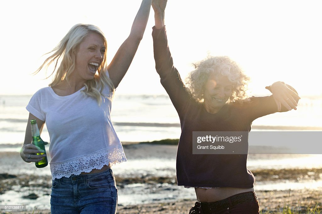 Mother and daughter dancing on Bournemouth beach, Dorset, UK : Stock Photo