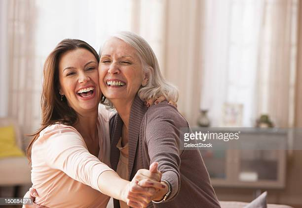 mother and daughter dancing - mid adult women stock pictures, royalty-free photos & images