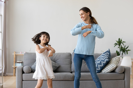 Mother and daughter dancing together in living room 1070262152