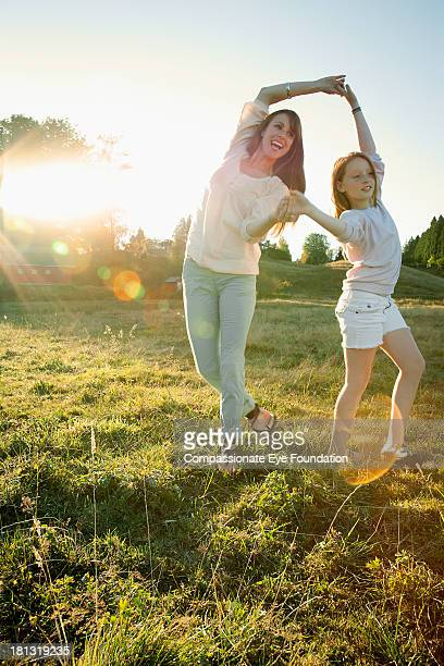 Mother and daughter dancing together outdoors