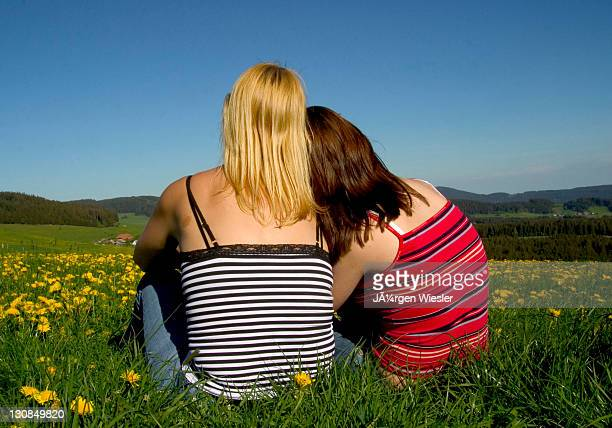 Mother and daughter daydreaming in a dandelion meadow, Breitnau, Black Forest, Germany, Europe