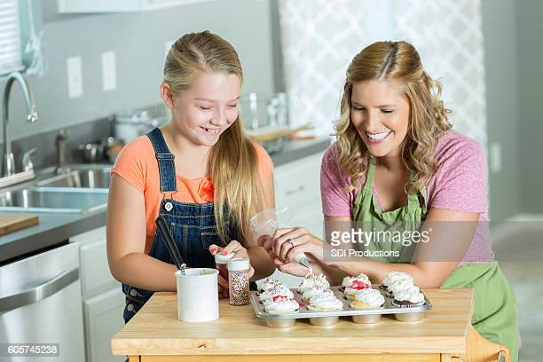 Mother and daughter decorate cupcakes together in kitchen