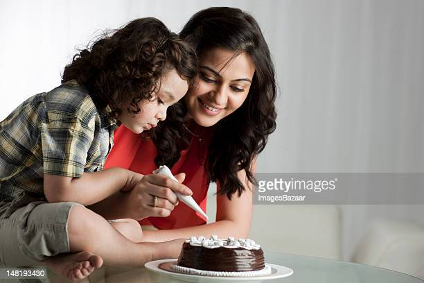 Mother and daughter (2-3) decorating cake
