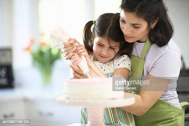 mother and daughter (4-5) decorating cake - decorating a cake stock pictures, royalty-free photos & images