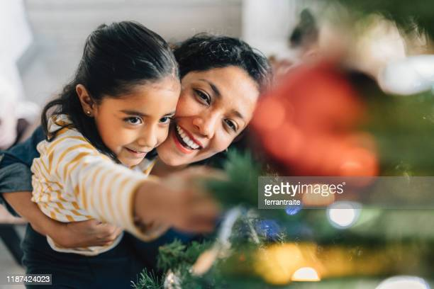 mother and daughter decorating christmas tree - mexican christmas stock photos and pictures