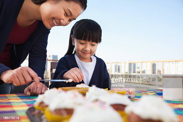 Mother and daughter decorating cupcakes