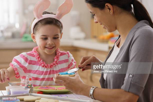 Mother and daughter decorating Easter cookies