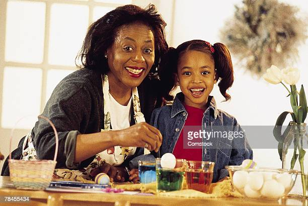 mother and daughter decorating easter eggs - african american easter stock photos and pictures