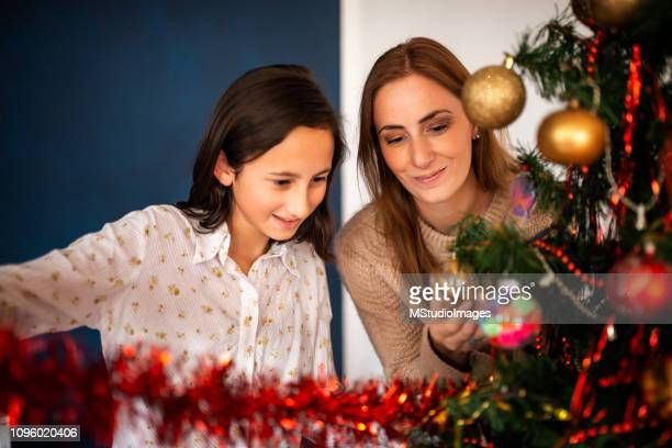 mother and daughter decorating the christmas tree - mexican christmas stock photos and pictures