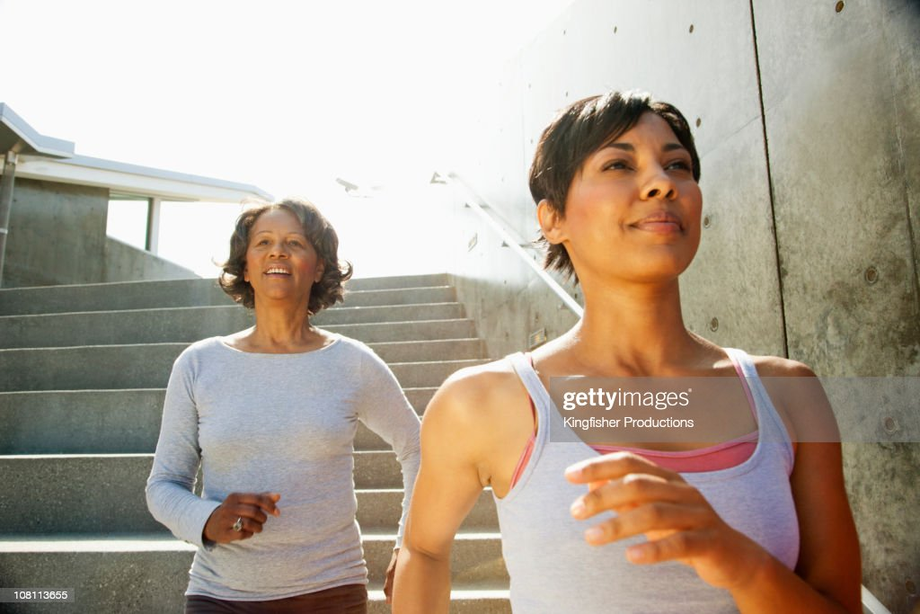 Mother and daughter descending urban steps : Stock Photo